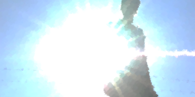 A person stands in shadow with the bright sun flaring behind her. The sky is blue.