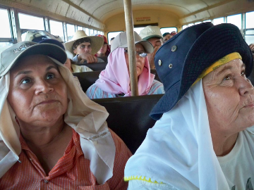 Two female farmworkers in a bus on their way to the fields.