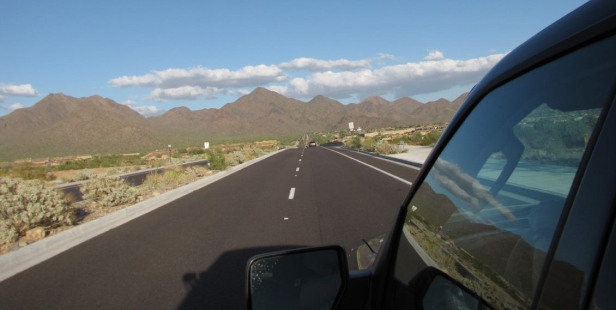 long, two-lane road through the desert, towards brown craggy mountains close on the horizon. Photo is taken out of a moving vehicle, the front driver's sider window and rearview mirror are in the right hand corner of the picture frame.
